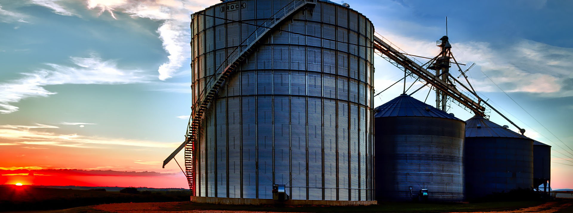 Grain silos in front of red sky